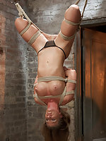 Suspended upside down by her knees, fucked and fisted